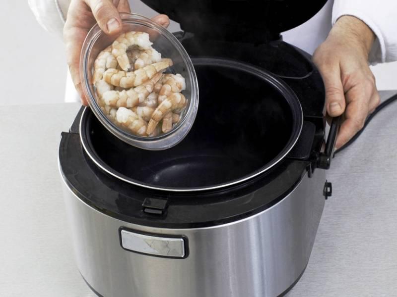 Доведите до кипения воду в мультиварке и отварите в течение 5 минут креветки, затем откиньте их ну дуршлаг. Порежьте огурец, лук и маслины.