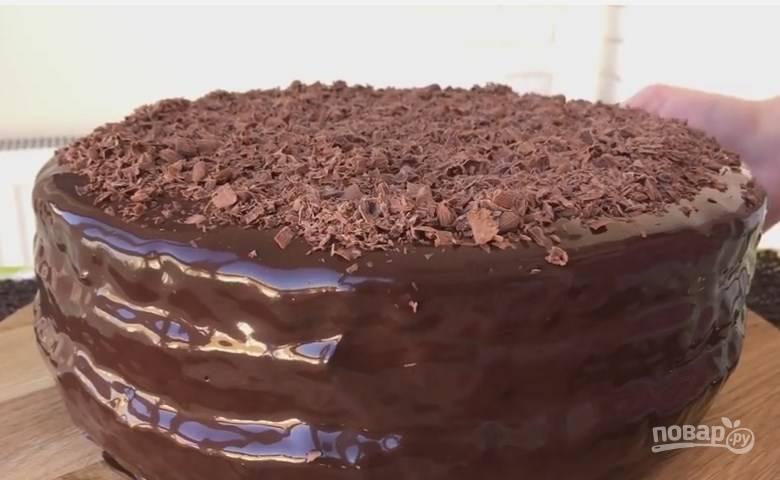 12. Перемазанный торт должен постоять в холодильнике 1 час. Потом перенесите его на решетку и обильно полейте помадкой. А сверху присыпьте шоколадной крошкой. Чтобы всё застыло, пусть торт снова постоит в холодильнике 2 часа.