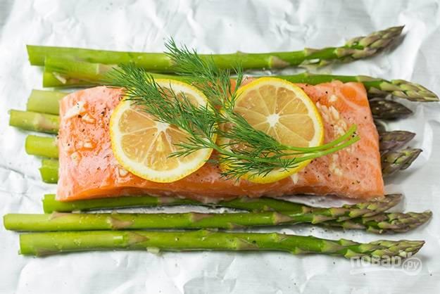 4.Посыпьте рыбку черным молотым перцем. Вымойте лимон и разрежьте его на тонкие кружочки, уложите по 2 кусочка на рыбное филе, добавьте 1-2 веточки укропа.