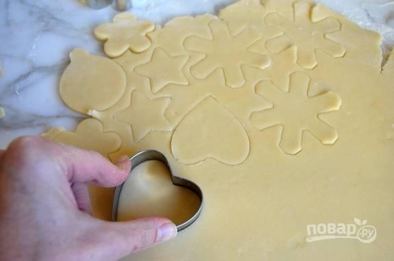 Теперь возьмите формы, вырежьте печенье из теста. Затем переложите изделия на противень с пергаментной бумагой.
