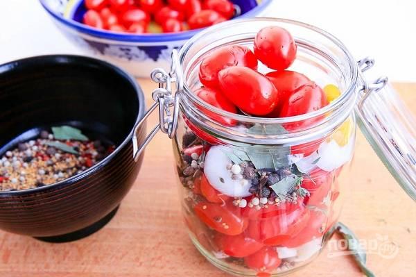 3. Наполните баночки помидорами, добавьте несколько ломтиков лука и чеснок, всыпьте специи. Залейте кипятком, прикройте крышками и оставьте на 3-4 минуты.