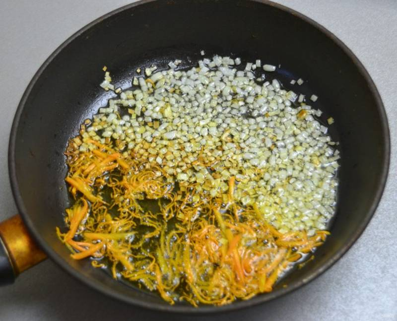 Сделайте зажарку из вторых половинок моркови и лука. Жарьте до золотистого цвета.