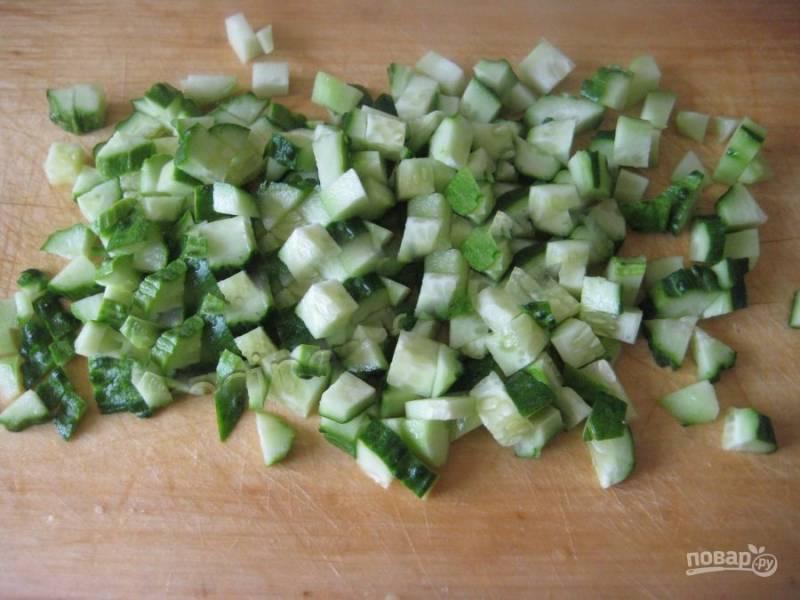 Нарежьте кубиками свежие огурцы.