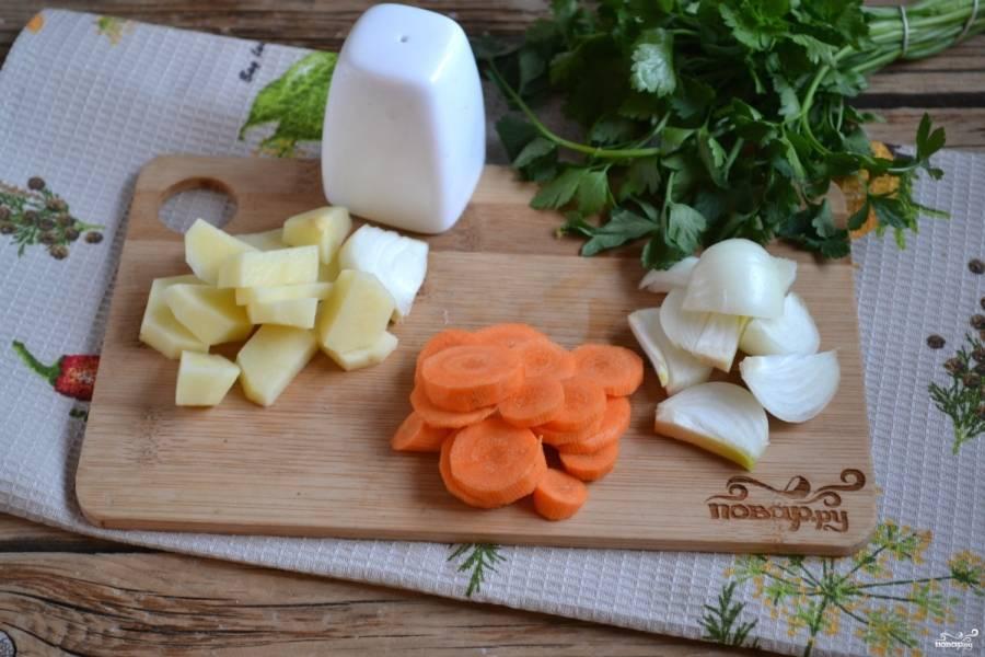 Картофель и лук порежьте небольшими кусочками, морковь порубите на кружочки. Отправьте корнеплоды в кипящий бульон и варите 15 минут.