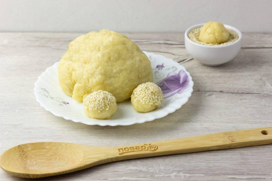 Отщипывайте кусочки теста размером с грецкий орех, скатывайте в шарик и одной стороной обваливайте в кунжуте.