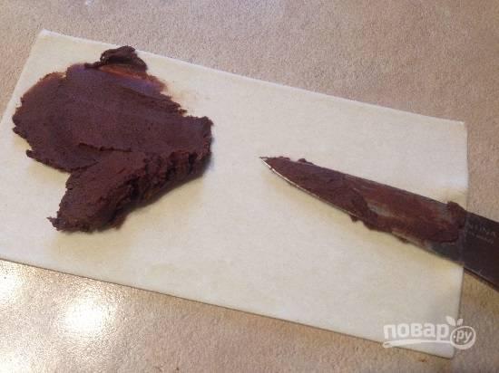 Выкладываем на один лист теста треть шоколадной помадки, размазываем её ножом по всей поверхности.