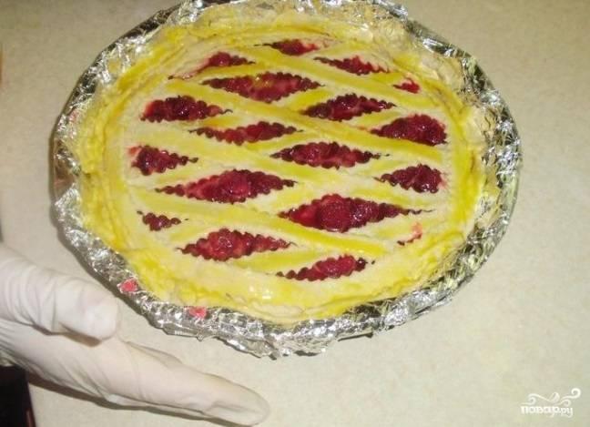 Смажьте дно с тестом яйцом для закрепления. Уложите на него начинку. Раскатайте второй кусок теста. Нарежьте его полосками, которые затем расположите решеткой поверх начинки. Закрепите края. Смажьте поверхность желтком, немного присыпьте сахаром.