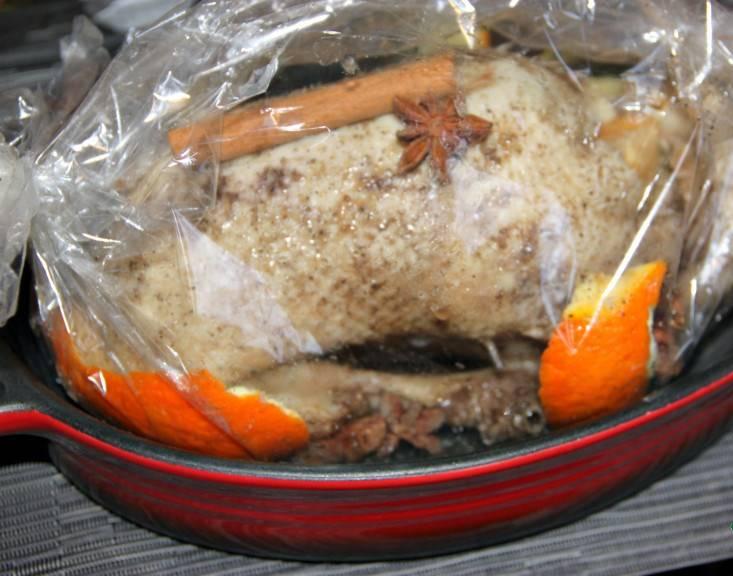 2. Апельсин чистим. Дольками фаршируем тушку изнутри, погружаем в пакет. Туда же - маринад, анис, корицу и шкурки апельсина. Завязываем края, отправляем в духовку, нагреваем до 140 градусах и держим в духовке 2,5 часа.