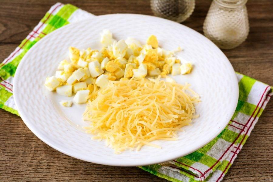 Сварите яйца вкрутую и нарежьте кубиками. Сыр натрите на терке.