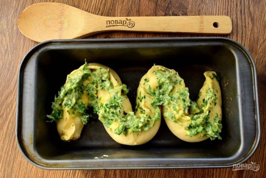 Поднимите края теста и  тщательно защипните по центру. Поместите колбаску из теста с начинкой в прямоугольную форму для запекания в виде зигзага.  Смешайте растопленное сливочное масло с чесночным порошком, измельченной петрушкой. Смажьте этой смесью верх теста.