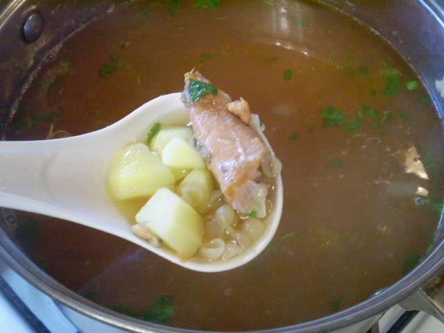 Добавляем в суп консервы и зелень. Варим еще 5-7 минут.