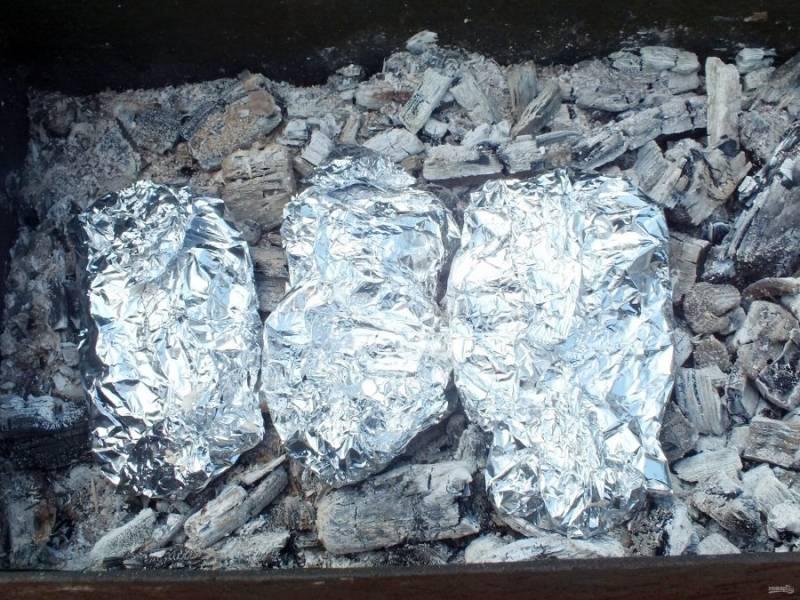 Выложите подготовленный картофель на горячие угли. Одновременно рекомендуется жарить шашлык. Запекайте картофель 30-40 минут.
