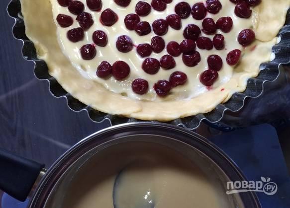 Вливаем в форму с тестом половину от всего количества крема. Сверху раскладываем вишни без косточек.