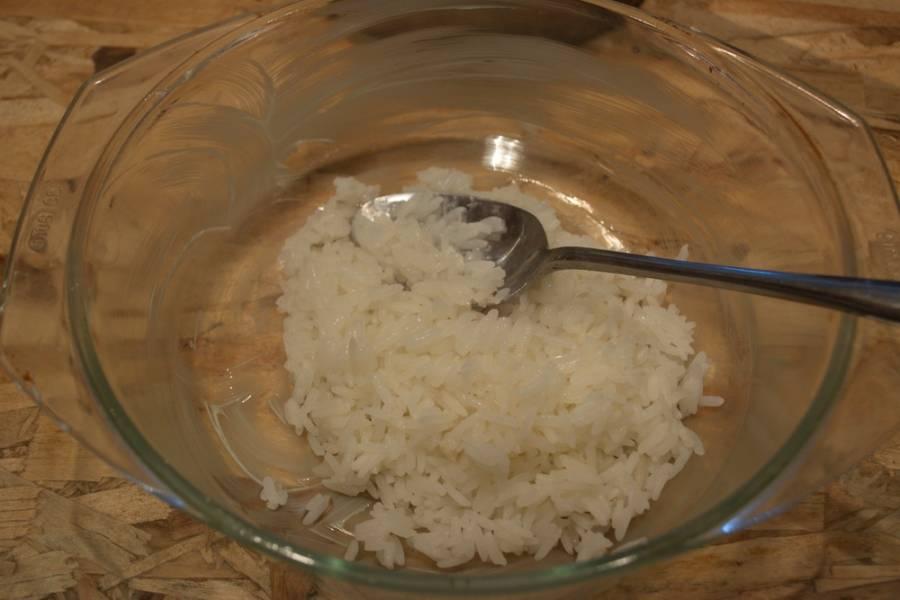 Форму для выпечки смазать маслом. Уложить на дно несколько ложек готового риса. Разровнять.
