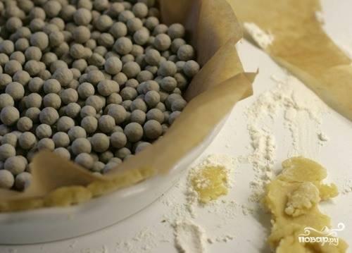 Смажьте форму для запекания растительным маслом, выложите туда раскатанное тесто, обрежьте все ненужное. Затем застелите тесто сверху пергаментом для запекания и насыпьте какой-то груз, чтобы корж при выпекании оставался ровным. Отлично для этой миссии подойдет горох или фасоль. Выпекайте корж 15 минут при ста девяноста градусах в духовом шкафу.