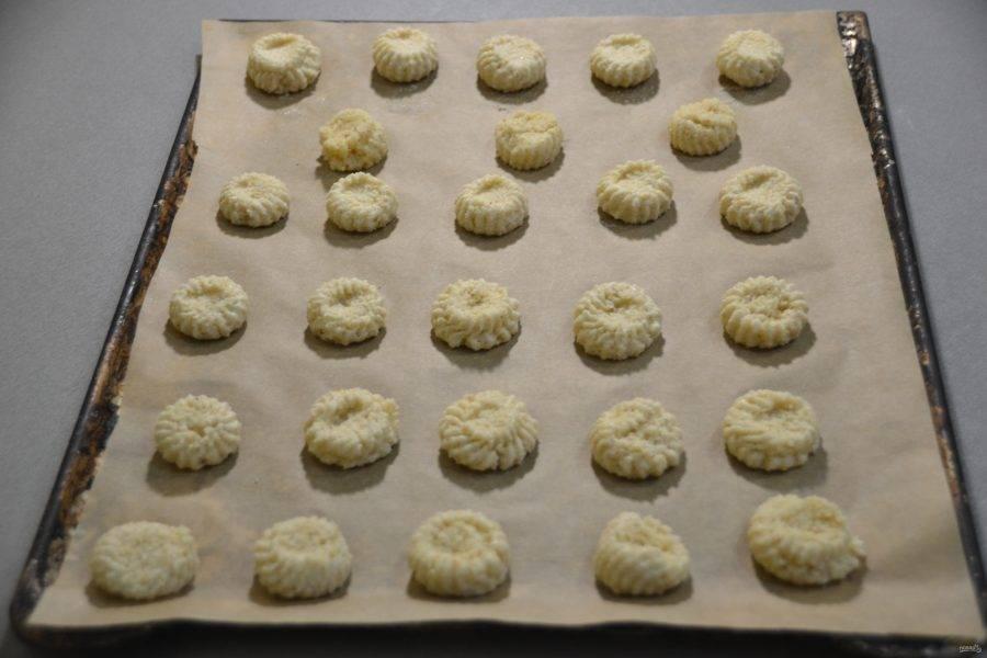 Выложите на пергамент для выпечки печенье, это можно сделать двумя маленькими ложками или с помощью кондитерского мешка. Оставляйте между печеньем небольшое расстояние.