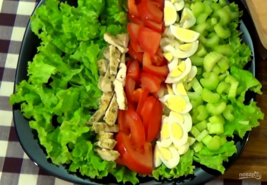 2. Перепелиные яйца отварите, очистите и разрежьте на четыре части. Выложите на листья салата. Небольшими пластинками нарежьте помидоры и обжаренное куриное филе (можно заменить ветчиной или копченой курицей). Выложите на листья салата.