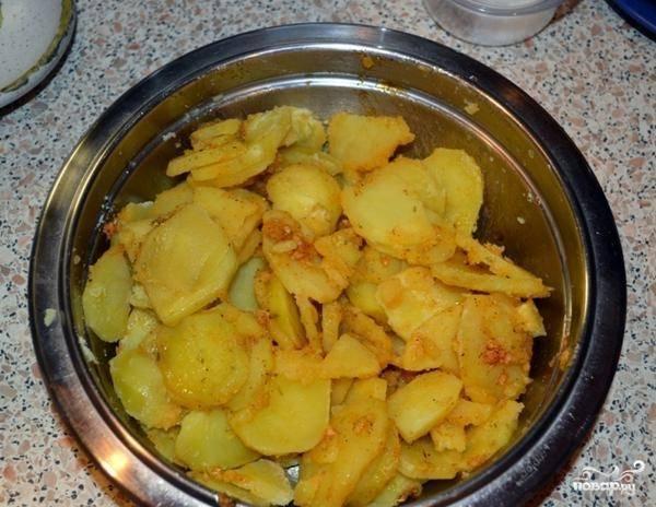 Затем слейте воду, а картофель хорошо перемешайте с соусом.