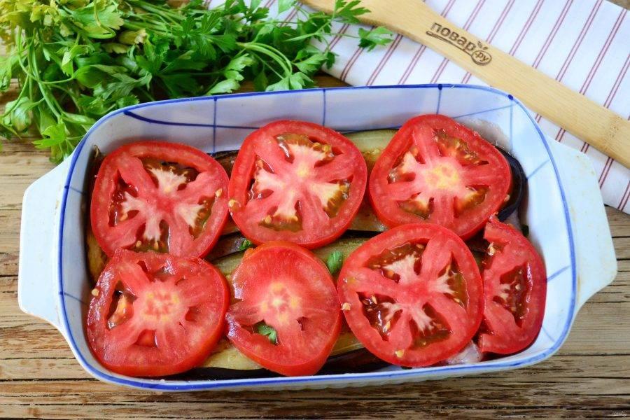Помидоры порежьте тонкими кружочками и выложите их на баклажаны. Отправьте блюдо в  духовку (температура — 180 градусов) и запекайте 25 минут.