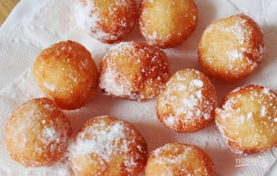 В казане или во фритюрнице разогрейте растительное масло без запаха. Затем обжаривайте в кипящем масле пончики, пока они не станут золотистого цвета. Готовые пончики выложите на салфетки, чтоб впитался лишний жир.