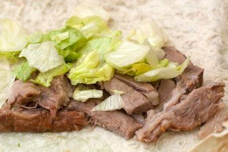 На лаваш выложите кусочки мяса и салат сдобренный маслом и специями.