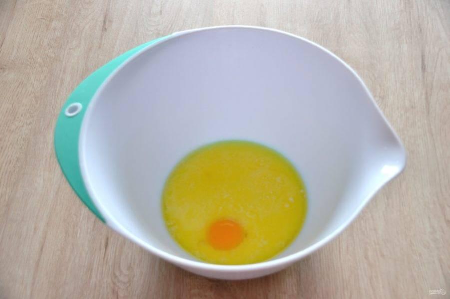 В миску для замешивания теста влейте растопленное сливочное масло, теплое молоко, яичный желток, смешайте.
