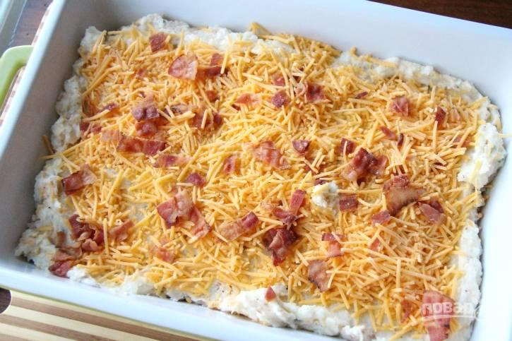 5. После этого выложите картофельную массу в форму для выпечки. Сверху натрите оставшийся сыр и разложите кусочки бекона.