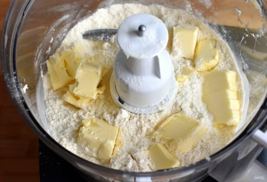 С помощью блендера пробейте в крошку охлажденное масло, нарезанное кубиками, муку, сахар, соль и разрыхлитель в пульсовом режиме.