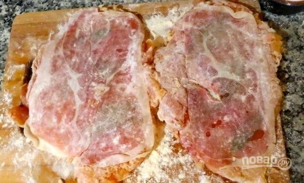 """Насыпьте в тарелку или на рабочую поверхность муку и равномерно ее распределите. Обмакните в муку каждый получившийся """"бутерброд"""" из мяса, ветчины и зелени. Если хотите, можете дополнительно скрепить конструкцию при помощи зубочисток."""