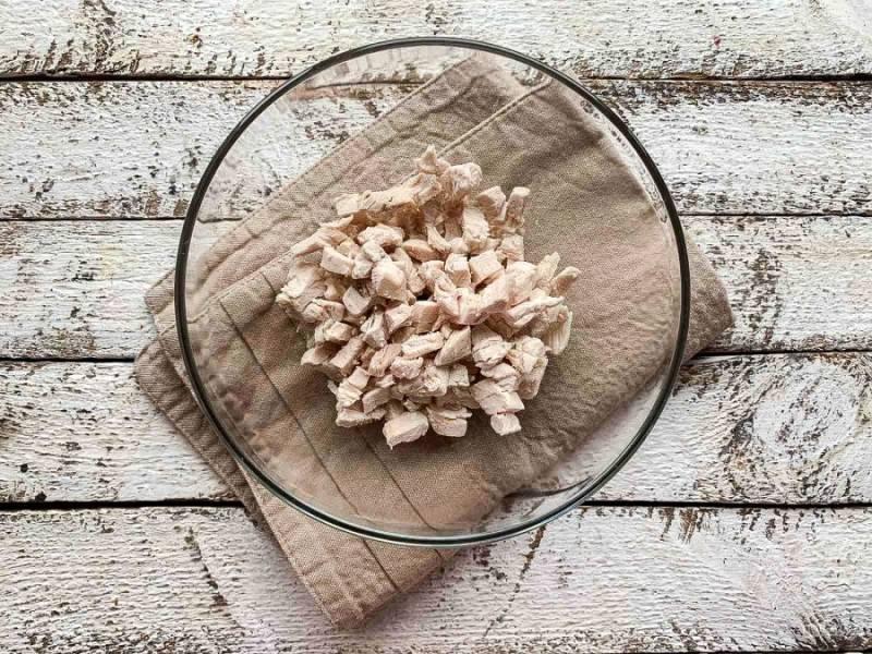 Куриное филе нарежьте небольшими кусочками и выложите в глубокую тарелку.