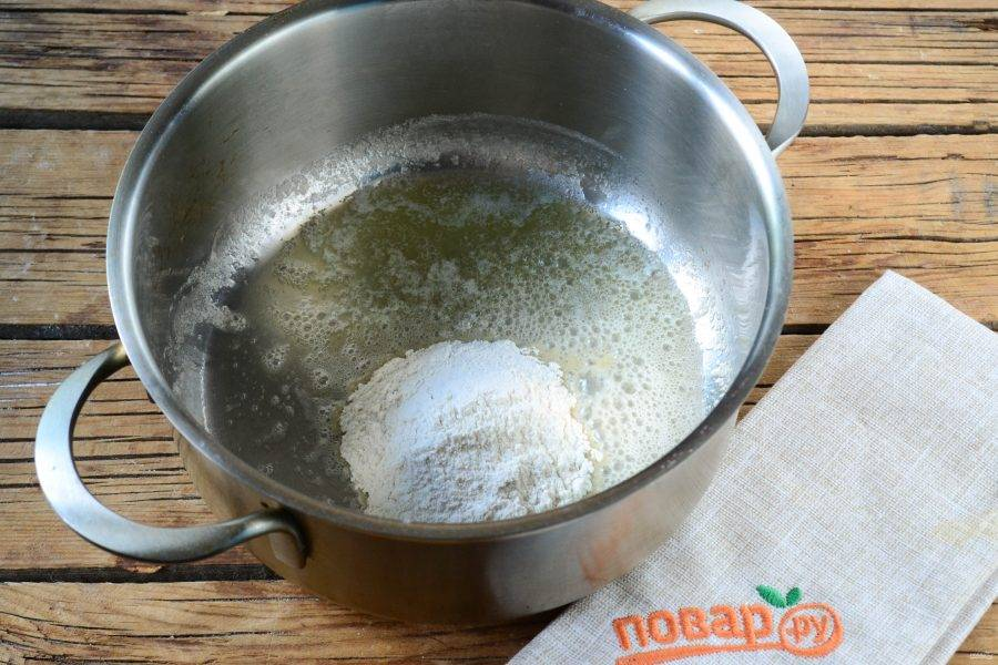 Начните с приготовления сливочного соуса. Для этого в небольшой толстодонной кастрюльке растопите сливочное масло. Добавьте к нему муку и энергичными движениями размешайте, чтобы мука полностью пропиталась маслом и заварилась.