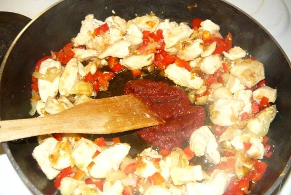 Теперь выкладываем томатную пасту, перемешиваем, жарим в течение минуты.