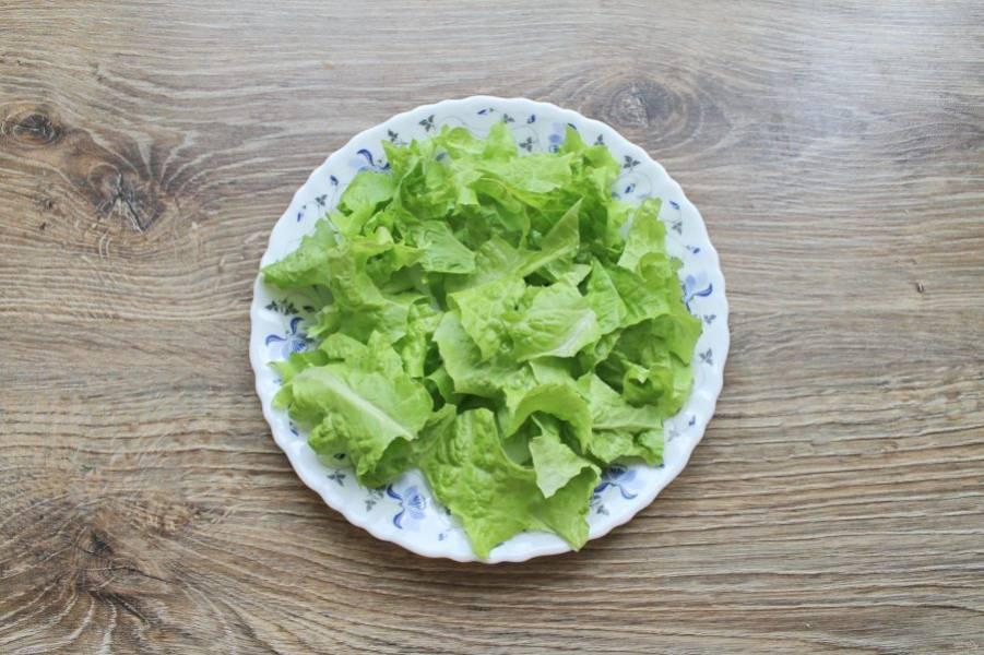 Листья салата порвите руками на мелкие кусочки и выложите на дно салатника.