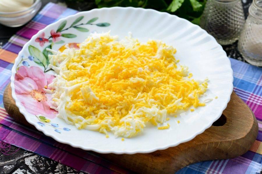 Сварите вкрутую куриные яйца, натрите их на средней или мелкой терке.
