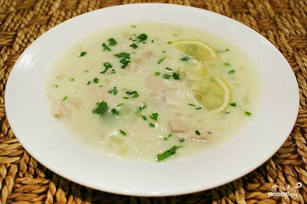 4. Уменьшите огонь. Добавьте в суп взбитые яйца и все тщательно перемешивайте в течение 2-3 минут. Суп должен немного загустеть. Разлейте его по тарелкам, украсив ломтиками лимона и нарубленной зеленью. Приятного аппетита!
