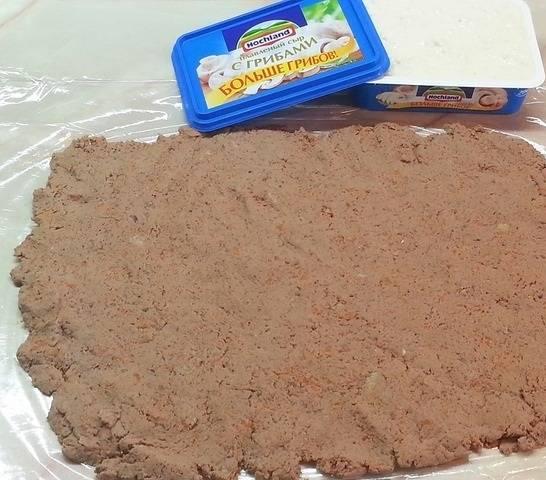 4. На рабочем столе расстелите лист пищевой пленки. Выложите фарш, разровняйте средним по толщине слоем.