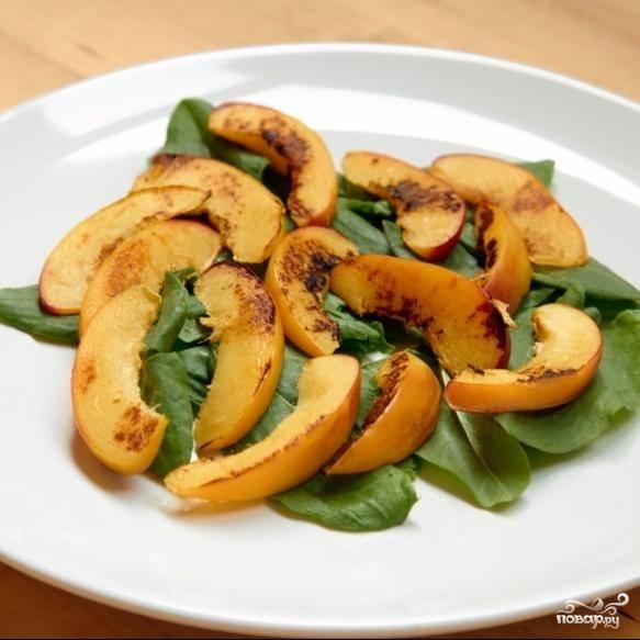 На сервировочную тарелку выкладываем мытые и сухие листья щавеля, сверху на них - обжаренные дольки персика.