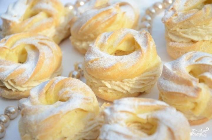 Готовые кольца из теста разрежьте вдоль, чтобы получилось две половинки. Каждую половинку промажьте толстый слоем творожного крема и соедините их. По желанию присыпьте получившиеся кольца сахарной пудрой.