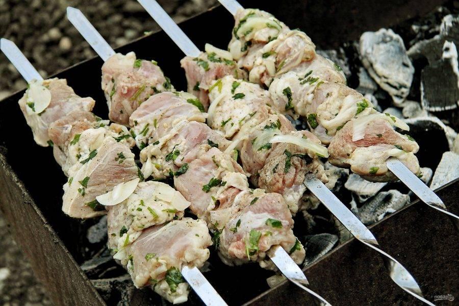 Мясо нанизайте на шампура и готовьте на мангале, периодически переворачивая до полной готовности.