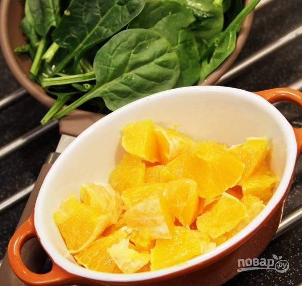 Сделайте салат. Промойте и обсушите шпинат. Апельсин очистите, удалите семечки и кожицу. Нарежьте фрукт кусочками.