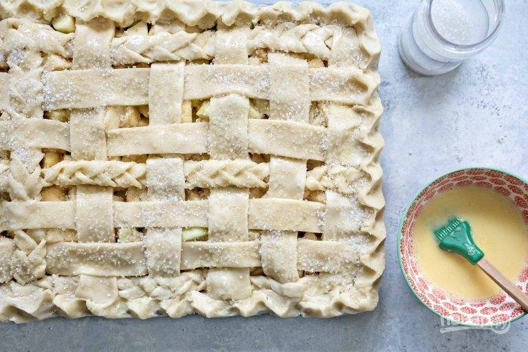 5.Достаньте остальное тесто и разрежьте его на тонкие полоски. Некоторые полоски переплетите в косичку, остальные оставьте так. Накройте начинку полосками, закрепите их по краям. Смешайте яйцо и молоко, смажьте верхушку.