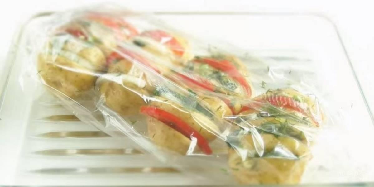 3. Фаршируйте картофель нарезанными помидорами, репчатым луком и зеленью, чередуя начинку. Выложите картофель в рукав для запекания и отправьте в разогретую до 180 градусов духовке на 1 час до готовности.