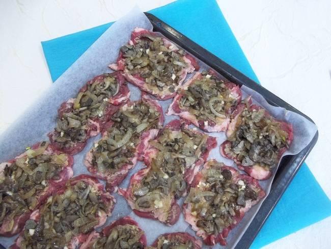 Затем посыпаем мясо мелко нарезанным чесночком. Сверху равномерно выкладываем обжаренные грибоки с луком.