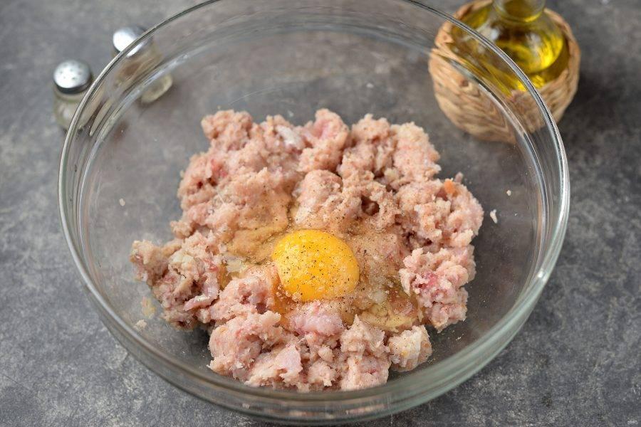 Переложите фарш в глубокую удобную миску, посолите и поперчите по вкусу, вбейте свежее куриное яйцо.