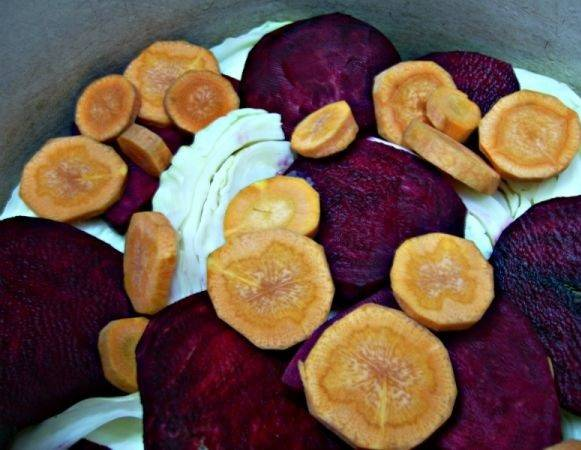 5. Очистите свеклу и нарежьте тонкими пластинками (можно натереть на терке). В этот простой рецепт капусты маринованной с чесноком и свеклой также используется морковь, но при желании ее можно не добавлять. Небольшую часть выложите в кастрюлю.