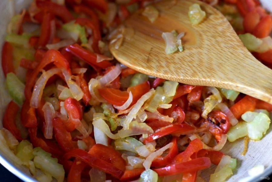 Одновременно пассеруйте на масле тонко нашинкованный лук и черешок сельдерея. Чуть позже добавьте к овощам сладкий перец и еще позже – острый  по вкусу.