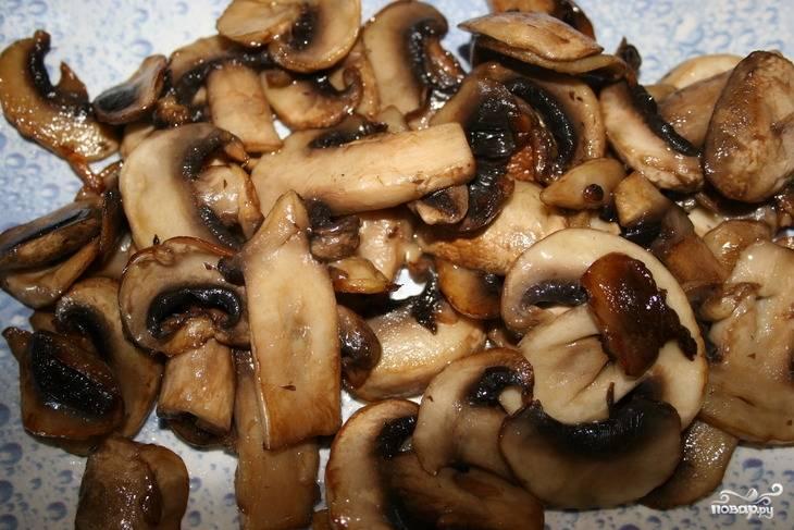 2.Сковороду ставим на огонь, наливаем немного оливкового масла, грибы очищаем, нарезаем пластинами и обжариваем до полной готовности. Выкладываем их на дно салатной тарелки.