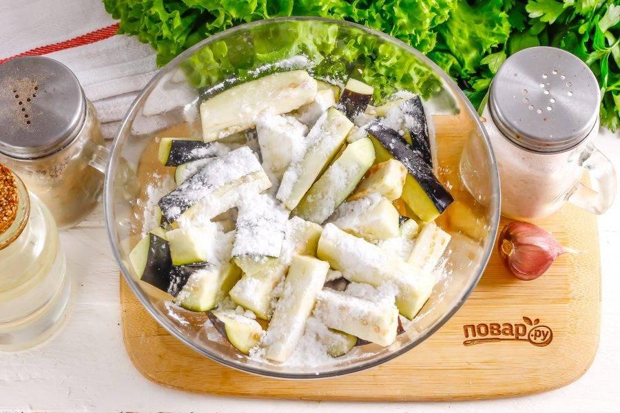 Всыпьте в емкость с баклажанами соль, молотый черный перец и кукурузный крахмал. Тщательно перемешайте.