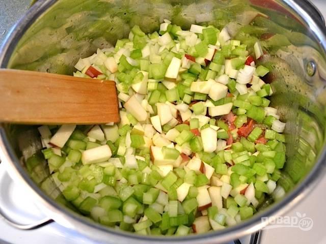 3.Помойте и почистите яблоки, удалите косточки и порежьте кубиками, почистите лук и порежьте небольшими кусочками, промойте сельдерей и нарежьте, почистите чеснок и измельчите его. Добавьте в кастрюлю с уже приготовленным беконом сельдерей, лук, яблоки и чеснок, перемешайте и готовьте 5 минут, пока овощи немного размягчатся.
