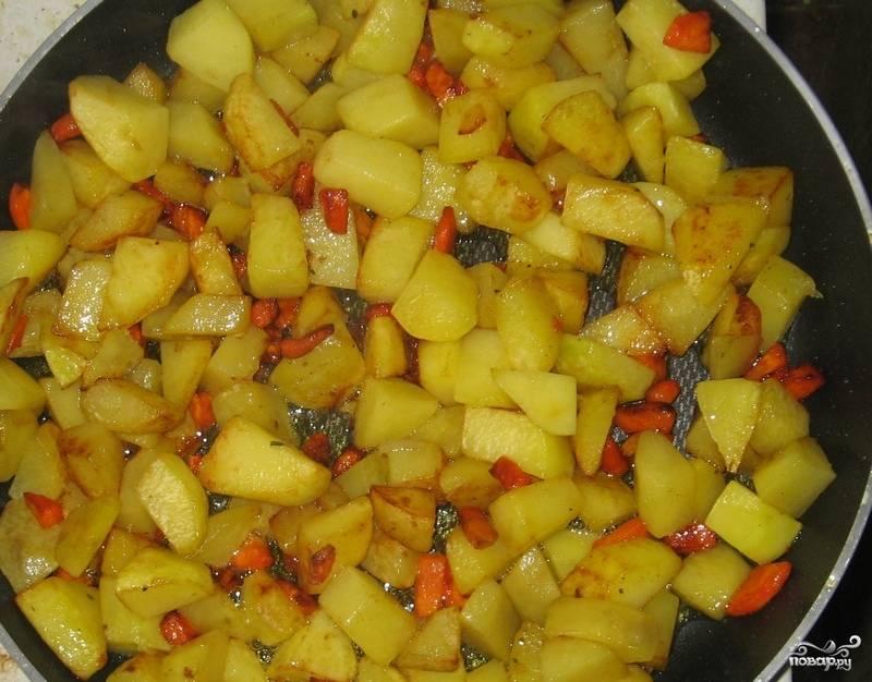 1. Картофель вымыть и почистить. Нарезать небольшими кубиками. Морковь очистить и порезать маленькими кусочками. На сковороду с высокими бортами налить растительное масло, хорошо разогреть его. Отправить туда овощи. Жарить на большом огне до появления аппетитной корочки. В конце посолить и поперчить по вкусу.